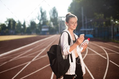 Cheerful girl with earphones happily using smartphone after training on racetrack of stadium