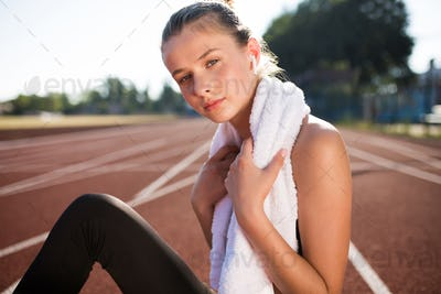 Beautiful girl with earphones and towel dreamily looking in camera after training at stadium