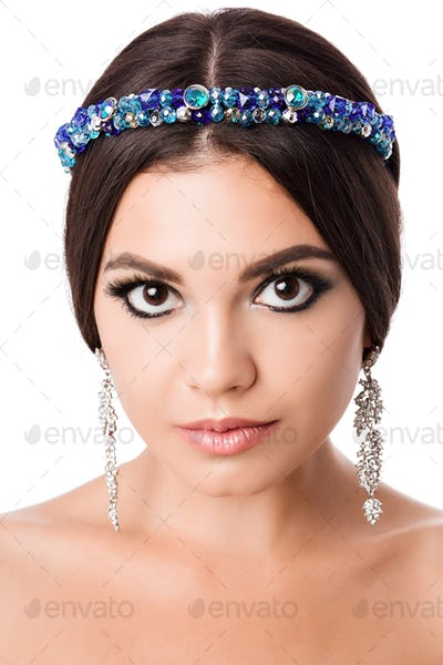Portrait of beautiful brunette woman with big earring and shinny accessories in hair. Perfect arabic