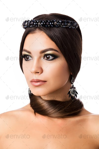 Portrait of beautiful brunette woman with big earring and shinny accessories. With hair around neck