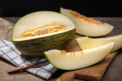 Fresh Muskmelon and slices on wooden table