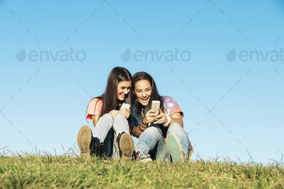 Two Teenage Girls Using Mobile In Park