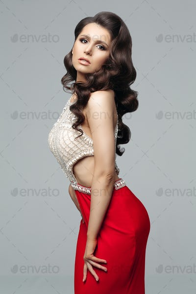 Seductive brunette woman in luxury dress with diamonds