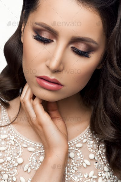Brunette in shine dress with perfect makeup, touching face