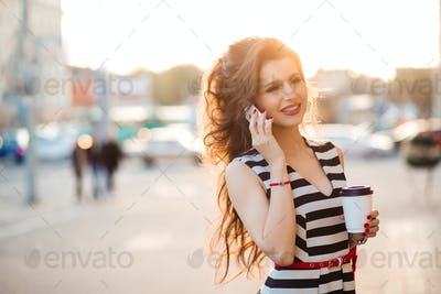 Beautiful brunette woman drinking coffee and talking to phone