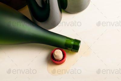 bottle in spilled cognac near empty wine bottles