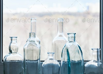 empty bottles and view of city park through window