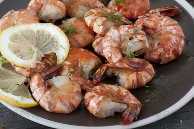 Baked shrimp with fresh tomato on a plate. Close up view.