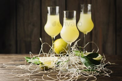 Iralian traditional liqueur with lemons on the vintage table