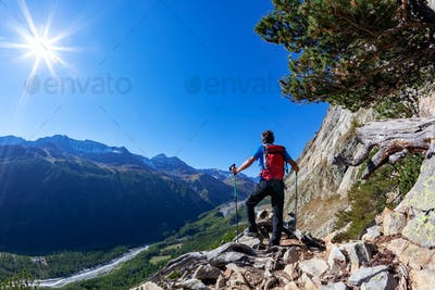 Hiker takes a rest observing a mountain panorama.