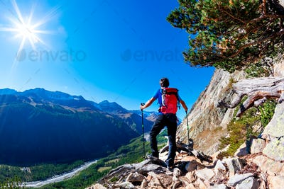 Hiker takes a rest observing a mountain panorama. Mont Blanc Massif, Italian Alps,