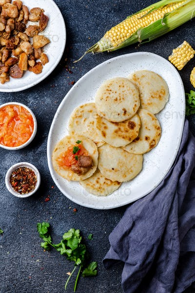 COLOMBIAN FOOD. Maize AREPAS and fried pork chicharron ans colombian tomato sauce. Top view. Black