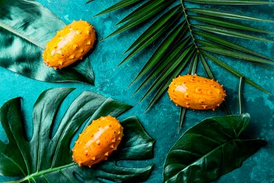 Tropical fruin KIWANO passion fruit in green bowl on turquoise background with tropical palm tree