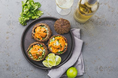 Fresh opened sea urchins. Caviar of sea urchins with onion, cilantro and lemon inside of shell of