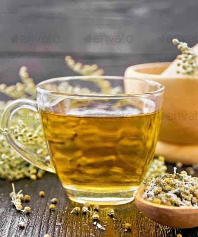 Tea of gray wormwood in glass cup with mortar on board