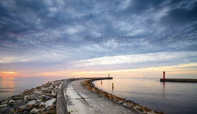 Rocky pier at the entrance to the harbor at sunset.