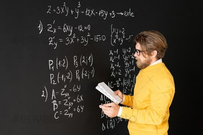 Bearded teacher in casualwear rewriting formulas on blackboard from his copybook