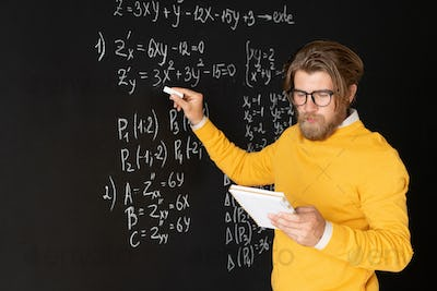 Serious teacher pointing at equation on blackboard with piece of chalk
