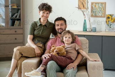 Happy young man with cute little son and his pretty wife sitting in armchair