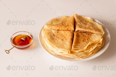 Four folded appetizing pancakes on stack of others on white porcelain plate
