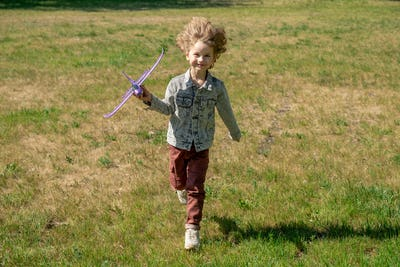 Happy cute little boy with blond curly hair holding toy airplane and running