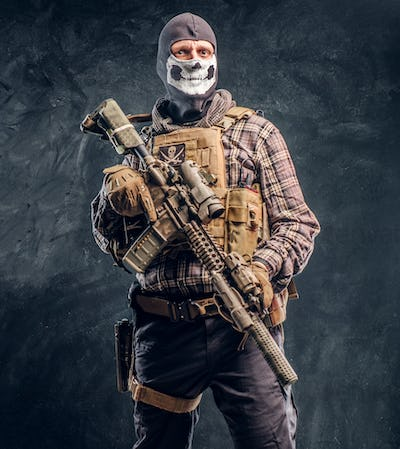 Private security service contractor wearing a balaclava skull holding an assault.