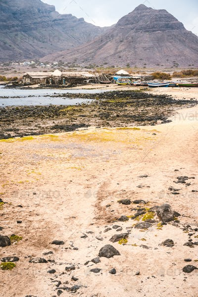 Mysterious landscape of sandy coastline with fisher village and black volcanic mountains in