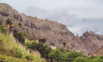 Local stone dwellings surrounded by tropical vegetation. Sharp mountain formation rising on the