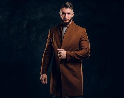 Portrait of a stylish male wearing the demi-season coat. Men's beauty, seasonal fashion