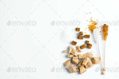Different types of sugar - brown cane, white, refined and crystal sugar stick on a white background