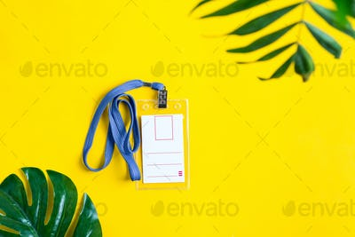 Plastic blank mock-up name tag on a yellow background with green tropical leaves. Top view