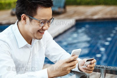 Young Handsome man enjoy shopping online on mobile phone with credit card