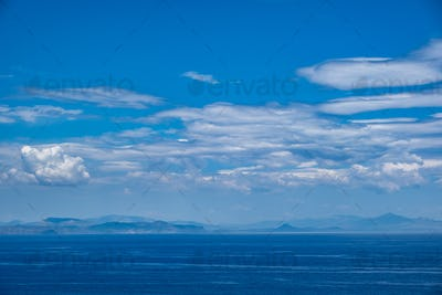 Blue sea and sky background, blue shades and white clouds