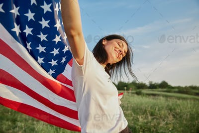 4th of July. American woman with the national American flag