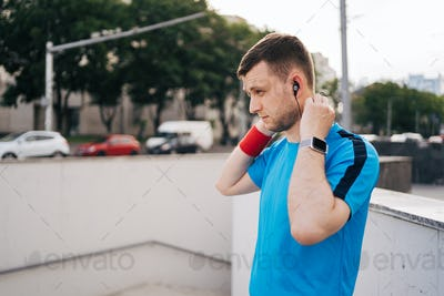 Man getting ready city workout arranging earphones