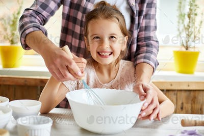 Mother teaching daughter prepare dough together in kitchen
