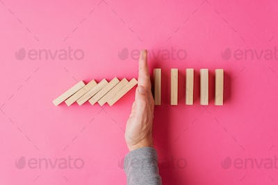 Top view of male hand interrupting collapsing dominos