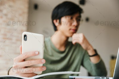 Image of handsome asian man using laptop and cellphone in apartment
