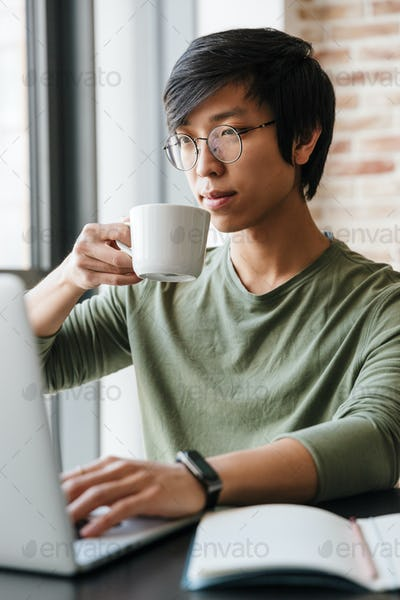 Image of asian man holding tea cup while using laptop in apartment