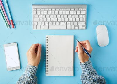 Faceless woman writing in notepad. Mobile phone with blank white screen display.