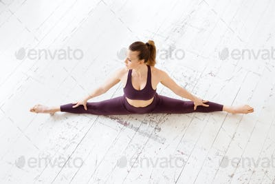 Athletic woman doing a frontal split yoga pose