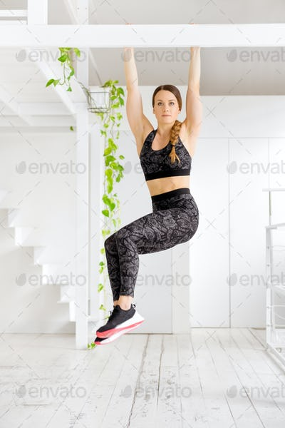Woman working out doing a toes to bar exercise