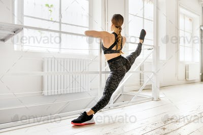 Woman doing a frontal split yoga pose using a bar