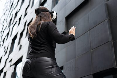Back Of Woman Wearing Virtual Reality Technology Glasses Against Modern Building