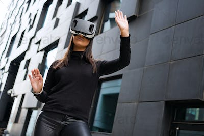 Woman Portrait Using Virtual Reality Glasses And Black Outfit In Futuristic City