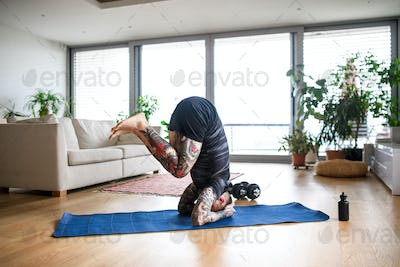 Young man doing workout exercise indoors at home, headstand