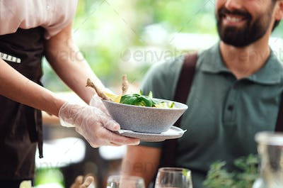 Unrecognizable waitres with gloves serving man outdoors on terrace restaurant