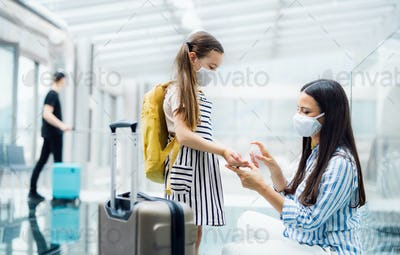 Mother and daughter with face mask going on holiday, disinfecting hands at the airport