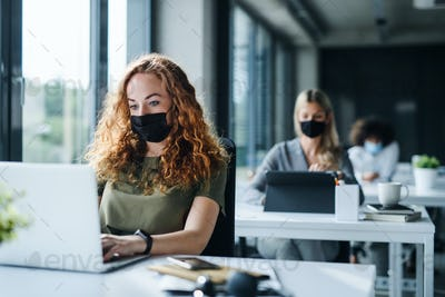 Young people with face masks back at work or school in office after lockdown