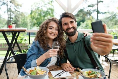 Happy couple sitting outdoors on terrace restaurant, taking selfie